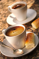 Two expresso coffees on granite, pastry and spoon on the side