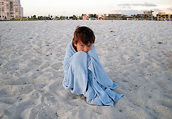 Young boy alone on the beach wrapped in a towel trying to get warm after swimming in the Gulf of Mexico. (Photo © Jock Fistick)