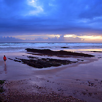 Dramatic sunset in Cornwall, England with teenager on beach