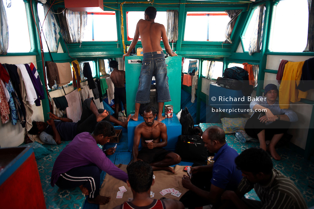 Writer Alain de Botton rests with resting crew after a day's tuna fishing aboard a traditional dhoni fishing boat on the Indian Ocean