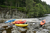 Colourful kayaks by river
