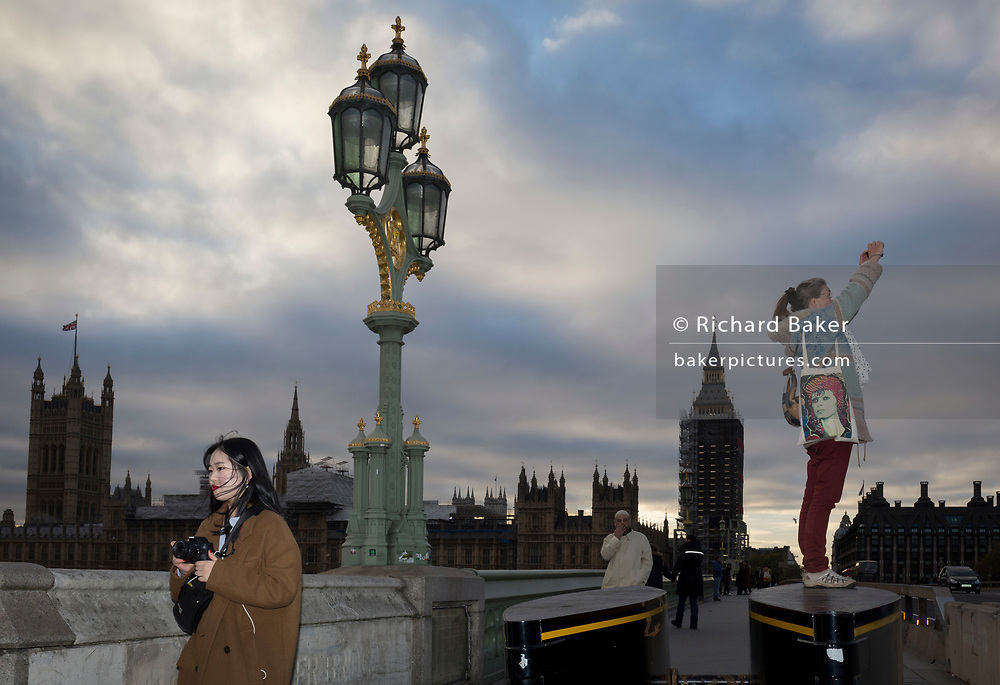 With the winter landscape of Westminster and the Houses of Parliament on the river Thames opposite, a woman with a David Bowie bag stands on the anti-terrorism security barriers at the southern end of Westminster Bridge, to take a picture of the London Eye, on 8th November 2017, in Lambeth, London.