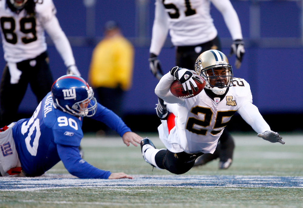 EAST RUTHERFORD, NJ - DECEMBER 24: Running Back Reggie Bush #25 of the New Orleans Saints runs with the ball as Ryan Kuehl #90 of the New York Giants defends  on December 24, 2006 at Giants Stadium in East Rutherford, New Jersey. The Saints defeated the Giants 30-7.