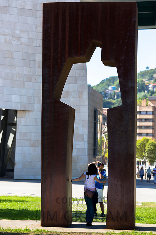 Tourists taking photographs through modern art by Guggenheim in Bilbao in Basque country, Spain