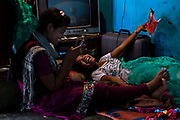 Poonam, 13, (left) is playing a game on the family's mobile phone while her older sister Jyoti, 14, is chatting with her and having fun with a carton box, on the floor of their newly built home in Oriya Basti, one of the water-contaminated colonies in Bhopal, central India, near the abandoned Union Carbide (now DOW Chemical) industrial complex, site of the infamous '1984 Gas Disaster'.