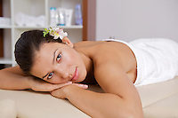 Portrait of young woman relaxing on massage table