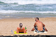 Israel, Haifa, Carmel Beach, Israelis go to the Beach on a warm, sunny day. Couple sunbathing on the beach