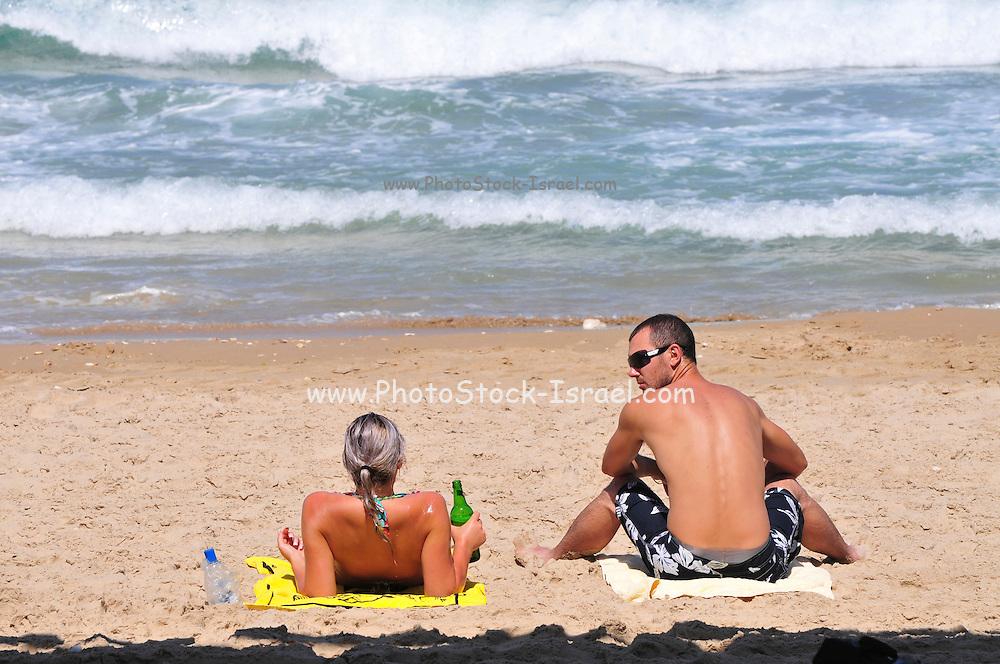 Israel, Haifa, Carmel Beach, Israelis go to the Beach on a warm, sunny day. Couple sunbathing on the beach