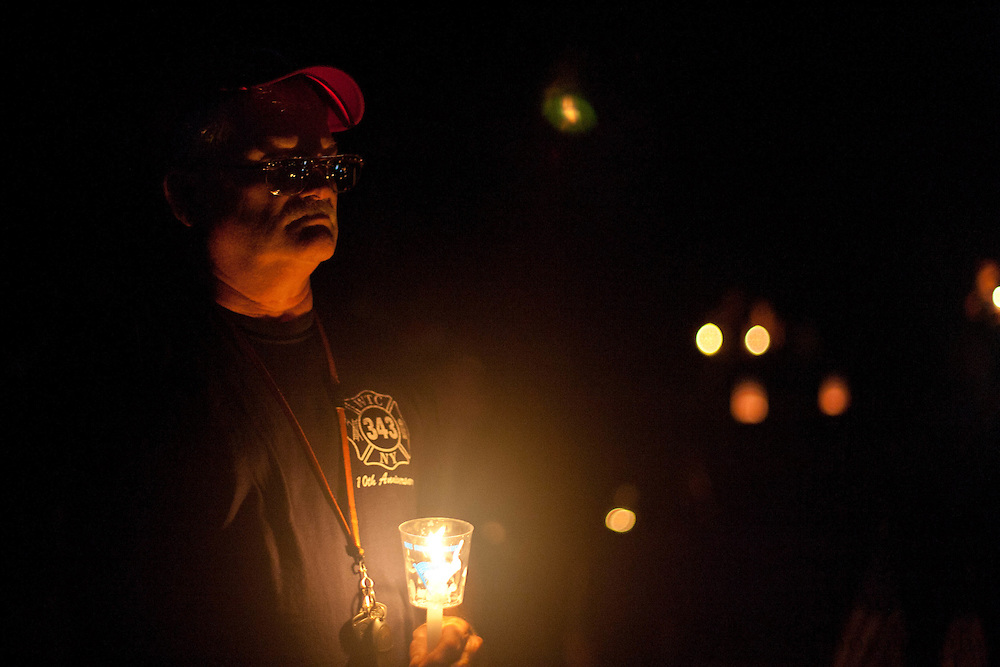 Warren Norris listens to a singer performing patriotic songs while standing at the 9/11 Memorial during a Candle Light Vigil held at Chestnut Branch Park in Mantua Saturday September 10.