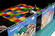 A brightly-coloured chequered table cloth and greasy menu choices seen in a cafe window in the North Somerset seaside town of Weston-super-Mare.