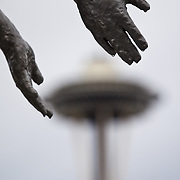 Hands from Father and Son fountain sculpture at the Seattle Art Museum Olympic Sculpture Park gently cradle the top of the Space Needle, Seattle, Washington
