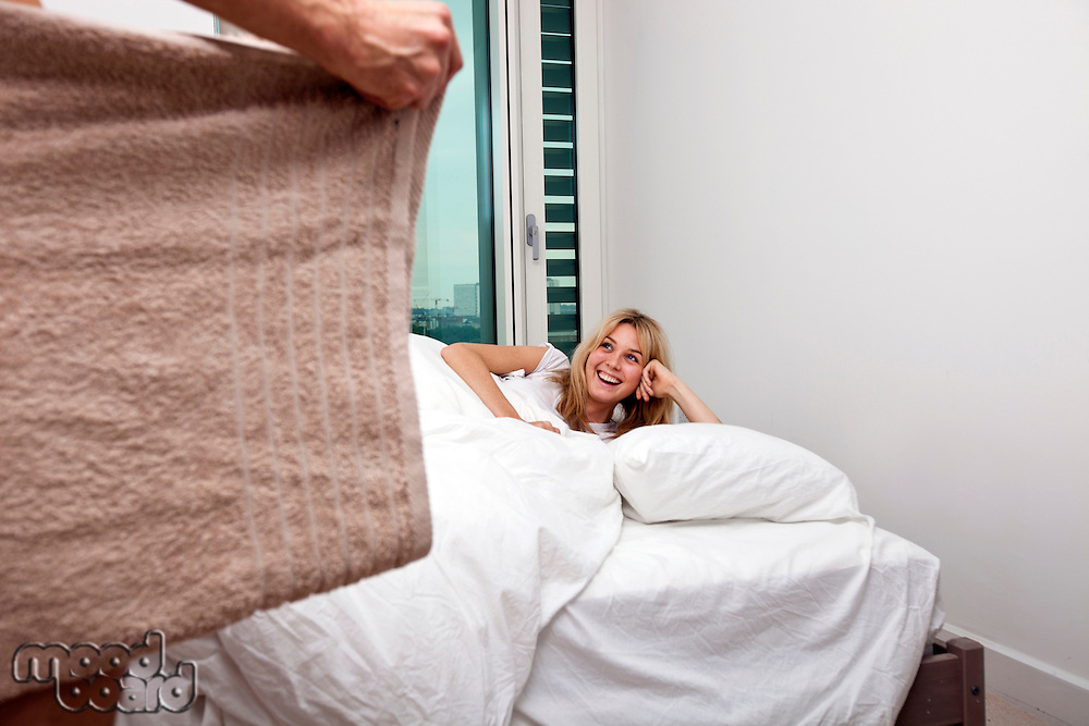 Happy woman looking at nude man holding towel in bedroom