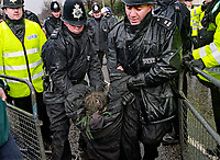 Police dragging away a protester  from an eco site after eviction , Crystal Palace, South London.