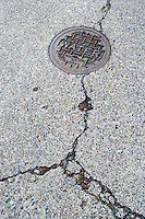 Cracks in a street surface around a water access cover.