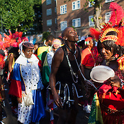 A black man is kept in a chain by a fellow dancer as part of the parade. The Notting Hill Carnival has been running since 1966 and is every year attended by up to a million people. The carnival is a mix of amazing dance parades and street parties with a distinct Caribbean feel.