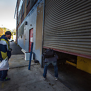 WASHINGTON, DC-OCT14: Leon Savoy (right), is the first to enter Capital Self-Storage, as he crawls under the gate as it opens in the morning, October 16,  2015, so he can get in his unit and change his clothes before heading to his job as a furniture restorer. Savoy is currently homeless and living at a nearby shelter. Many of the area homeless have possessions they want to keep safe, just nowhere permanent to live, so they store their belongings at Capital Self-Storage, where an upper-level unit costs $30/month. Some of the homeless patrons also spend their days in their storage units, when shelters are closed during midday hours. The storage facility near 3rd and Florida Avenue in Northeast, Washington, DC, is about to be replaced by a boutique hotel. (Photo by Evelyn Hockstein/For The Washington Post)
