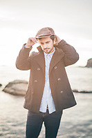 Tilt-shift (selective focus) portrait of stylish man in mid 20s wearing a peacoat and cabby hat at the coast.