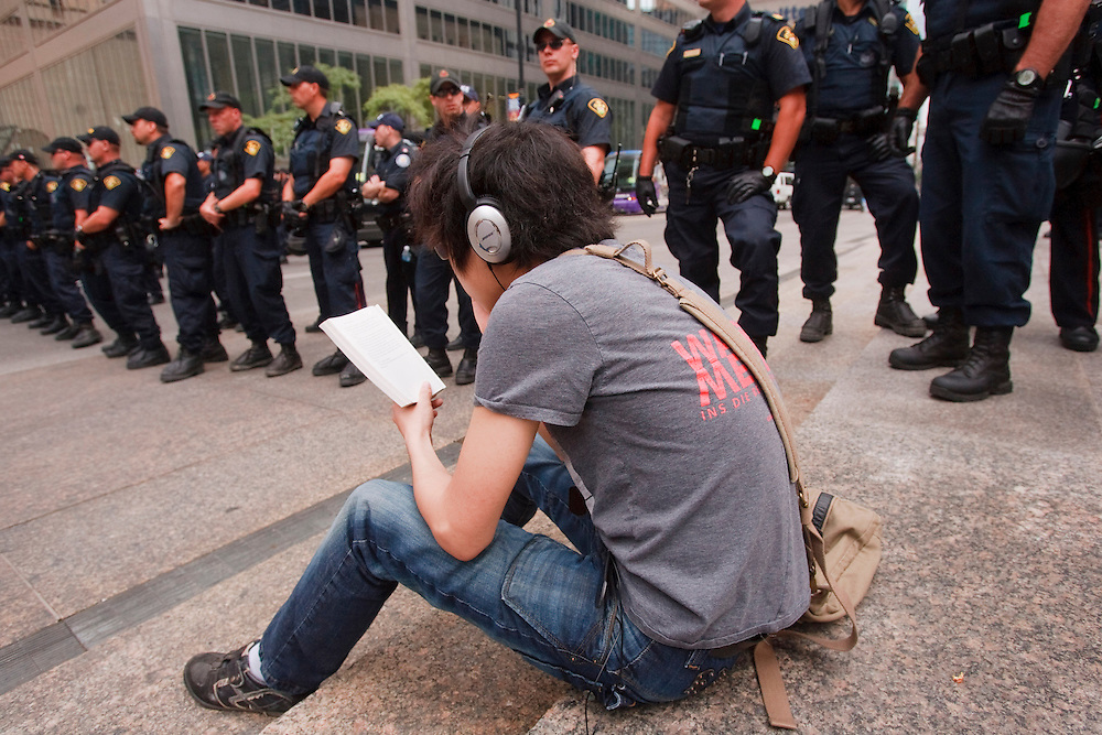 A man with headphones reads a book as dozens of police create a human baracade during a peaceful protest in the financial district of Toronto, Canada during the final day of the G20 summit June 27, 2010<br /> AFP/GEOFF ROBINS/STR
