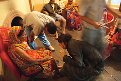 They don't have to wait long. Soon, several women in rainbow-hued saris are waiting at the door. Word is out that free treatments are being offered at the Red Cross.