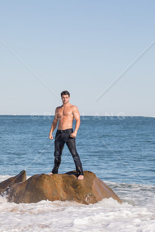 shirtless good looking man in wet jeans on a rock in the ocean
