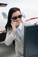 Mid-adult businesswoman using mobile phone outside of airplane.