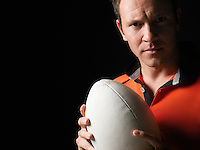 Rugby player holding ball close-up portrait