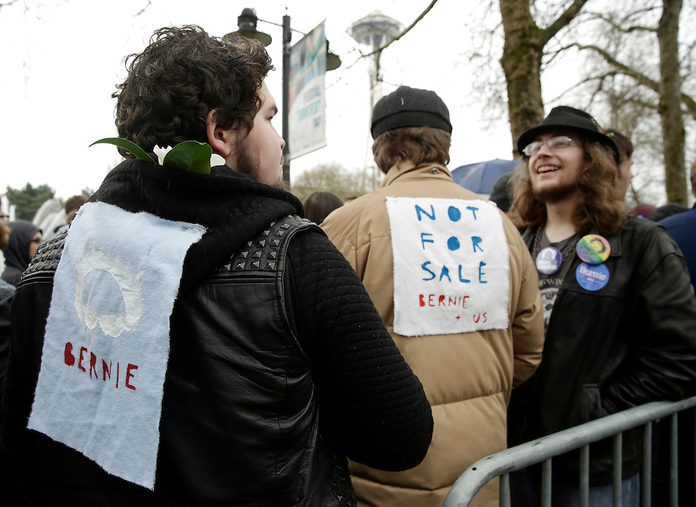 Friends Oscar Stern (L-R), 19, Robert Hendren, 18, and Henry Strayer, 18, all of Seattle, wait in line to see Democratic presidential candidate Bernie Sanders speak at Key Arena on March 20, 2016 in Seattle.  AFP PHOTO/JASON REDMOND