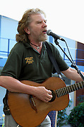 Tommy Sands with a guitar on stage, at an outdoor music festival in Israel Tommy sands is a singer songwriter and social activist from Ireland, May, 2006
