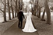 Sepia toned photo of a bride and groom walking in between a lane of trees on the Colgate University campus, Hamilton, NY