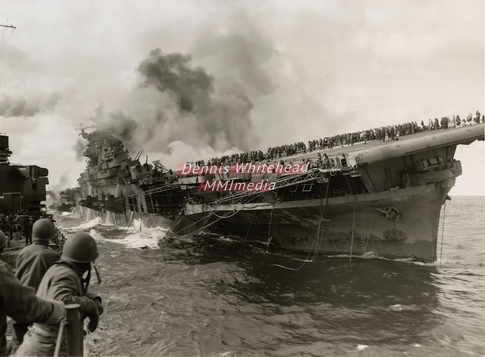 March 10, 1945 - The USS Santa Fe lays alongside the USS Franklin to render assistance after the aircraft carrier had been hit by a Japanese dive bomber. Original caption note: Not a Kamikaze)