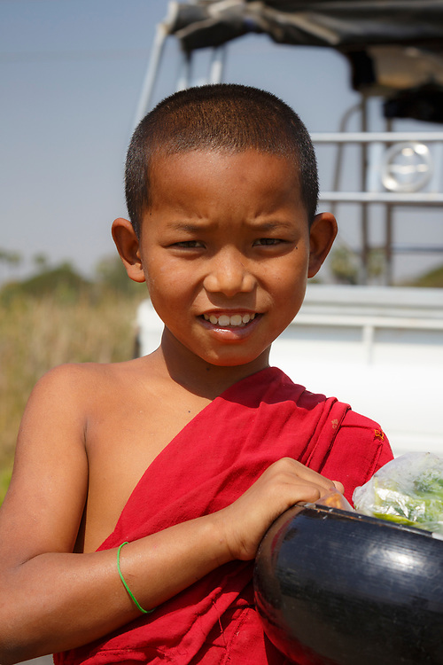 Young monk collecting alms on the road to Mandalay