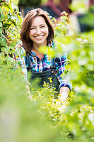 Portrait of smiling mature beautiful shop owner standing against plants