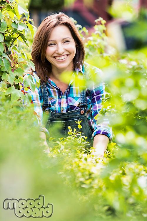 Portrait of smiling mature beautiful shop owner standing against plants
