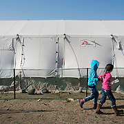 Two refugee girls walk past the MSF tent where they ear;tier they received snacks and bottled water, at the petrol station near Idomeni. In the last few months the fields near this petrol station have become a transit camp for thousands of refugees and migrants waiting to cross to Greek Macedonian border.