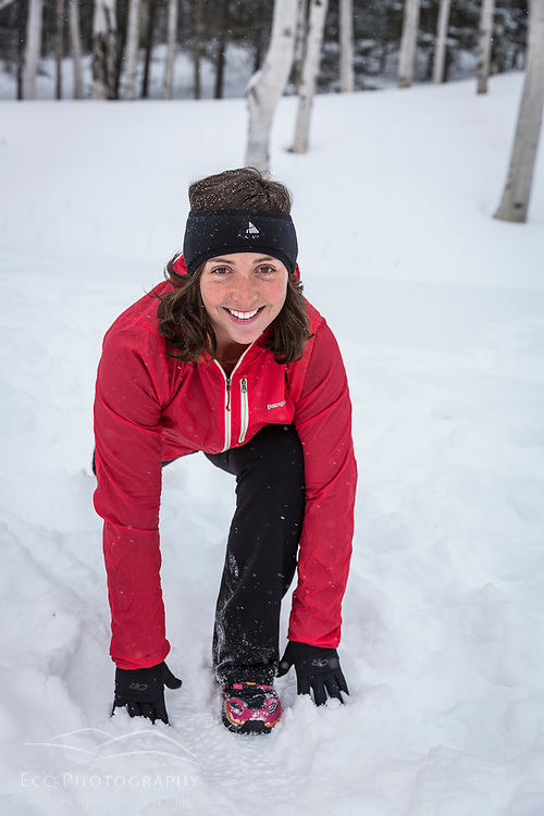 A woman stretches after running in New Hampshire's White Mountains on a snowy winter day.