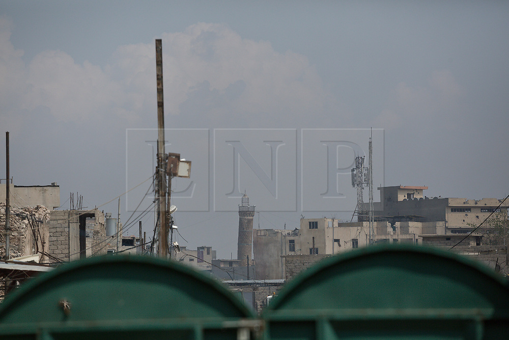 Licensed to London News Pictures. 02/04/2017. Mosul, Iraq. The minaret of the Al-Nuri Mosque, where ISIS leader Abu Bakr Baghdadi declared the group's caliphate in 2014, is seen from a recently liberated West Mosul garden.<br /> <br /> Iraqi forces continue to fight house to house as they push further into West Mosul. Iraqi forces are now advancing on the city's old districts where Islamic State fighters still hold out. Photo credit: Matt Cetti-Roberts/LNP