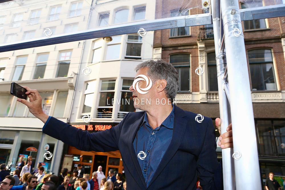 AMSTERDAM - In het Tuschinski Theater is de filmpremière Spijt. Met hier op de foto  Leopold Witte die met zijn iPhone probeert een foto te maken van zijn dochter op de rode loper bij Tuschinski. FOTO LEVIN DEN BOER - PERSFOTO.NU