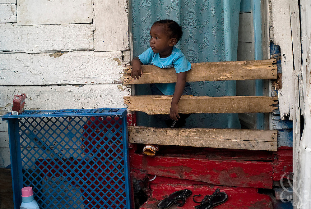 A baby plays in a makeshift playpen in a tenement yard June 15, 2008  in the Southside area of Kingston, Jamaica. A recent United Nations report found that the great majority of victims of violent crime in Jamaica live in ghetto areas, and suffer disproportionately high rates of unemployment, limited clean water supplies and electricity.
