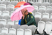 A spectator sheltering under an umbrella as the rain continues to fall during the International Test Match 2019 match between England and Australia at Lord's Cricket Ground, St John's Wood, United Kingdom on 14 August 2019.