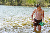 Girl (7-9) standing knee-deep in lake holding fishing net.