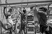From left: Mona, Oscar and Pete hoist the wooden frame at their camp at Wood Street and 26th Street on Thursday, June 15, 2017, in Oakland, Calif. The frame will be used to hold a cover for shade.
