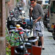 NLD/Amsterdam/20110511 - Bridget Maasland en broer stallen hun scooter