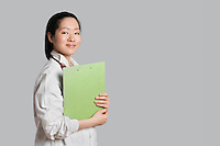 Portrait of a confident Asian female doctor holding clipboard over gray background