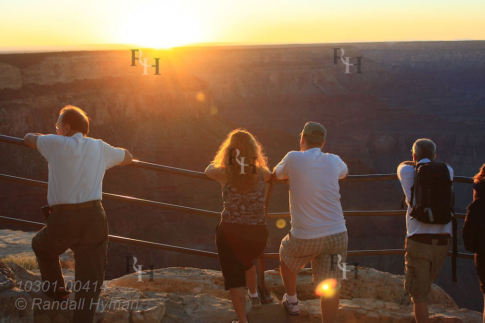 Four tourists admire late September sunset at Mohave Point overlook on South Rim of Grand Canyon National Park, Arizona.