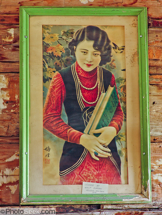 "A portrait of a Chinese woman hangs in a late 1800s restored frontier cabin in Nevada City, Montana, USA. In 1870, Chinese people (nearly all male) made up 10% of the territorial population of Montana. Territorial laws prohibited ""China Men"" from owning placer claims, so they mined the leavings of others or performed laundry or domestic service, which was always in great demand. Today, Nevada City contains several fascinating Chinese buildings built about 1890, mostly moved here from Butte, Montana. Nevada City was a booming placer gold mining camp from 1863-1876, but quickly declined into a virtual ghost town. This fascinating town inspires you to imagination what life must have been like in early Montana when gold was discovered at nearby Alder Gulch. More than 90 buildings from across Montana have been gathered for preservation at Nevada City, mostly owned by the people of the State of Montana, and managed by the Montana Heritage Commission. In 2001, the excellent PBS television series ""Frontier House"" used one of the buildings and its furnishings to train families in re-creating pioneer life. A miner's court trial and hanging of George Ives in the main street of Nevada City was the catalyst for forming the Vigilantes, a group of citizens famous for taking justice into their own hands in 1863-1864. Directions: go 27 miles southeast of Twin Bridges, Montana on Highway 287."