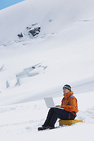Hiker using laptop on snowy mountain peak