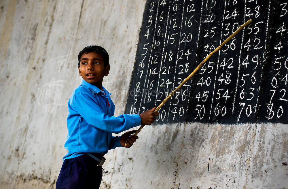 22nd April 2013, Shakarpur, New Delhi, India.  A boy reads from a blackboard out loud for other pupils to repeat at a makeshift school under a metro bridge near the Yamuna Bank Metro station in Shakarpur, New Delhi, India on the 22nd April 2013. <br /> <br /> Rajesh Kumar Sharma (40) and Laxmi Chandra (45), started this makeshift school a year ago. Five days a week, he takes out two hours to teach when his younger brother replaces him at his general store in Shakarpur. The students are children of labourers, rickshaw-pullers and market gardeners. This is the 3rd site he has used to teach under privileged children in the city, he began in 1997 fifteen years ago. <br /> <br /> PHOTOGRAPH BY AND COPYRIGHT OF SIMON DE TREY-WHITE<br /> <br /> + 91 98103 99809<br /> + 91 11 435 06980<br /> +44 07966 405896<br /> +44 1963 220 745<br /> email: simon@simondetreywhite.com<br /> photographer in delhi<br /> journalist