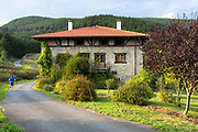 Runner passes Casa Rural Ametzola hotel traditional Basque architecture in the Biskaia Basque region of Northern Spain