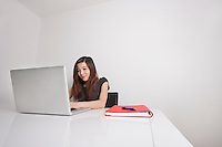 Confident young businesswoman using laptop at office desk
