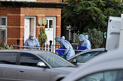 © Licensed to London News Pictures. 20/02/2018. LONDON, UK.  A forensics team prepare to enter a house in Halliday Square, Southall, West London, after a 26 year old man was fatally stabbed outside in the square on the afternoon of 19 February.  A 39 year old man was arrested at the scene and is in custody.  Investigations are ongoing.  Photo credit: Stephen Chung/LNP